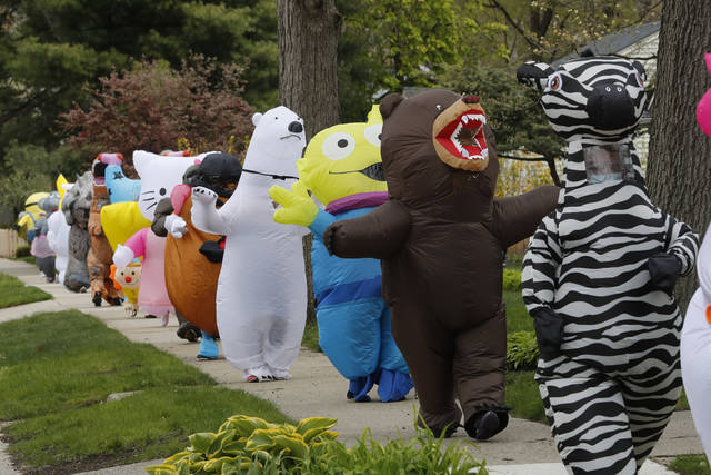 In this Monday, May 11, 2020 photo, members of the T-Rex Walking Club walk through a neighborhood in Ferndale, Mich. While the club members get a kick out of their strolls through town, the idea is to bring a little bit of cheer to their fellow residents who remain under quarantine as part of Gov. Gretchen Whitmer's stay-at-home order due to the COVID-19 pandemic. (AP Photo/Carlos Osorio)