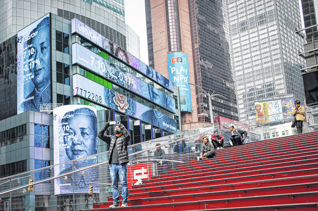 Pedestrians can be seen in a sparsely populated Times Square in New York. COVID-19 has shaken theater fans and shuttered all New York City's venues, including Broadway. How Broadway — one the city's jewels — will reopen is still not clear.