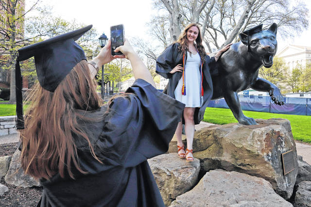 Class of 2020 University of Pittsburgh graduates Shannon Trombley, left, of Philadelphia, and Julie Jones, of West Chester, Pa., take turns posing for photos April 27 with a statue of Pitt's mascot, the Pitt Panther.
