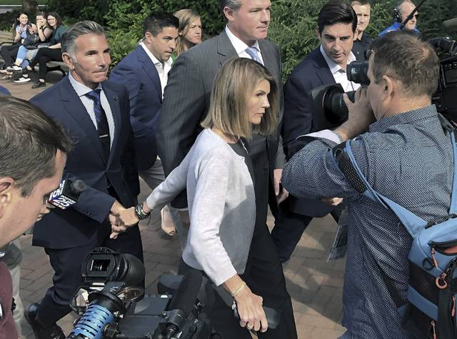 Lori Loughlin and her husband, clothing designer Mossimo Giannulli, left, pleaded guilty in a video arraignment Frida to charges of trying to secure the fraudulent admission of their two children to the University of Southern California as purported athletic recruits.