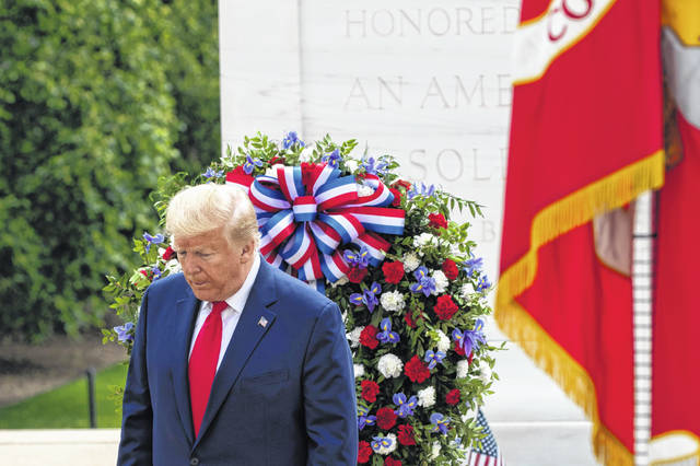 President Donald Trump turns after placing a wreath at the Tomb of the Unknown Soldier in Arlington National Cemetery, in honor of Memorial Day on Monday in Arlington, Va.