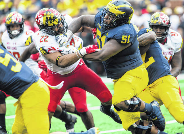 In this Oct. 6, 2018, file photo, Maryland inside linebacker Isaiah Davis (22) is blocked by Michigan offensive lineman Cesar Ruiz (51) in the second quarter of an NCAA college football game in Ann Arbor, Mich. Ruiz, who was selected by the New Orleans Saints in the first round of the NFL draft this year, is one of four offensive lineman that need to be replaced.