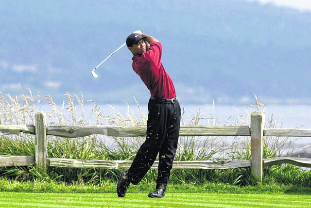 In this June 18, 2000, file photo, Tiger Woods tees off on the 18th hole on his way to winning the 100th U.S. Open Golf Championship at the Pebble Beach Golf Links in Pebble Beach. Woods won in the Champions for Charity event Sunday.