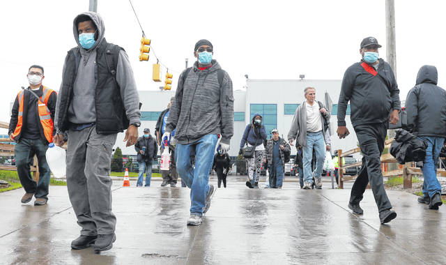 United Auto Workers members leave the Fiat Chrysler Automobiles Warren Truck Plant after the first work shift, Monday, May 18, 2020, in Warren, Mich. Fiat Chrysler Automobiles NV along with rivals Ford and General Motors Co., restarted the assembly lines on Monday after several week of inactivity due to the corona virus pandemic.
