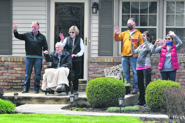 Former Allen County commissioner Dan Reiff waves to participants of a drive-by-parade past his home in Elida. Staff at Allen County Children Services and employees from various Allen County offices came together in April to show their support and offer encouragement.