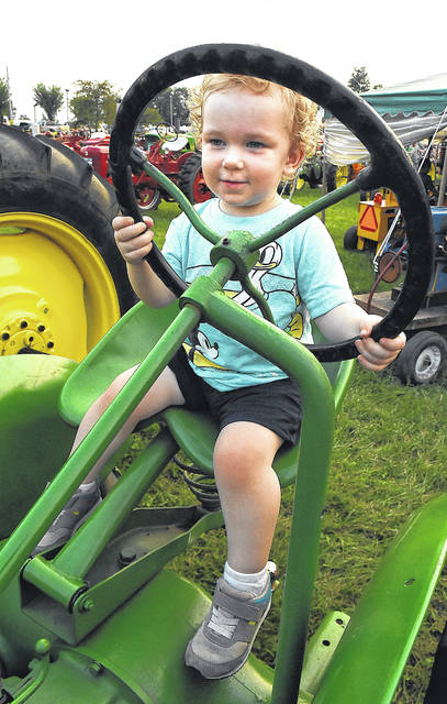 Miles Dellinger, 2, of Euclid, holds the steering wheel of a John Deere tractor at the Allen County Fair last year.