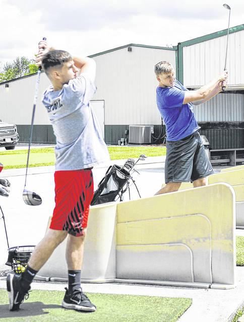 Stephen Tafloinger, left, and Mark Janowski use the driving range at Swing Rite Driving Range and Golf Shop on Saturday morning.