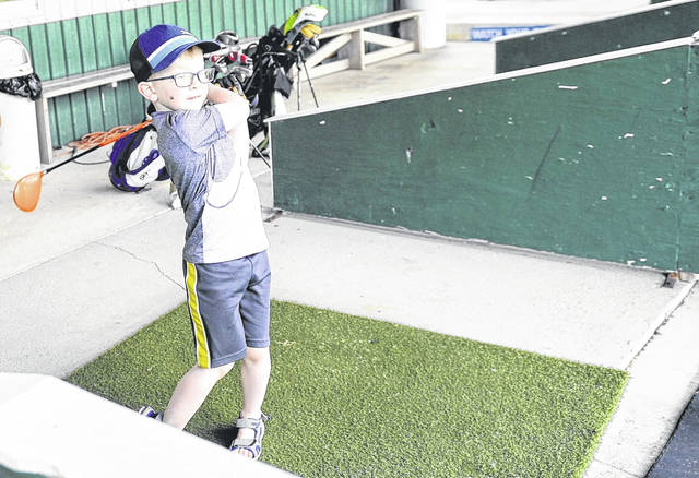 Thomas Mitchell, 6, watches his shot on the driving range at Swing Rite Driving Range and Golf Shop on Saturday morning.