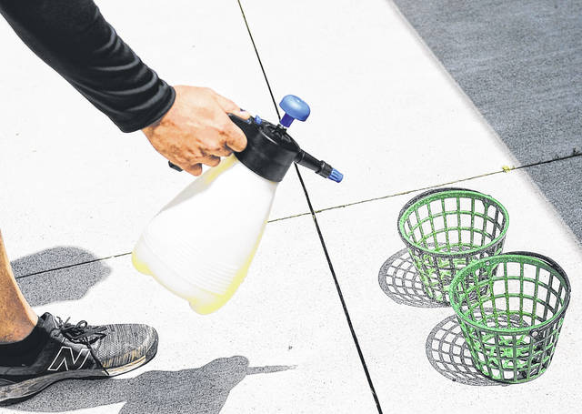 Owner Mike Harmon sprays disinfectant spray on baskets at Swing Rite Driving Range and Golf Shop on Saturday morning.