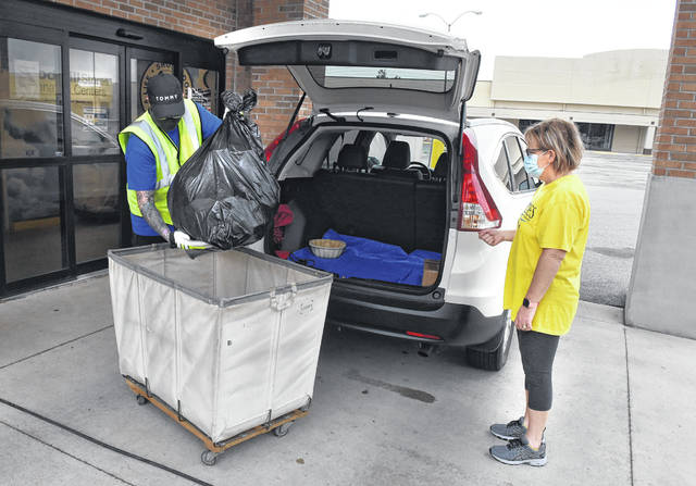 Goodwill employee Tylor Fugatt unloads a donation at the Goodwill Store on Allentown Road in Lima. Area thrift stores reported seeing more donations and higher sales in the midst of the coronavirus pandemic.