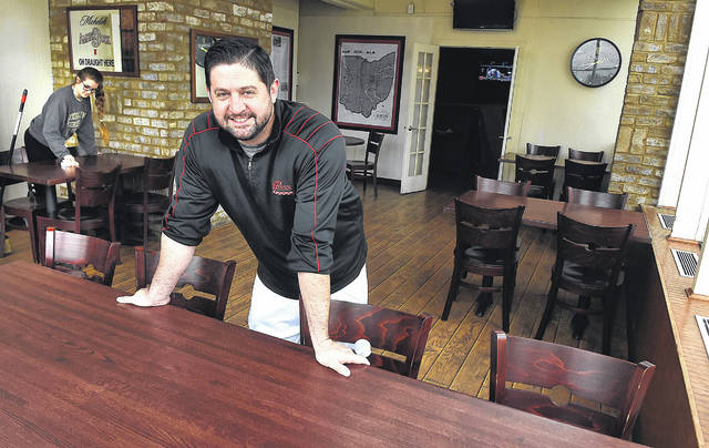 Lock Sixteen Steakhouse manager Scott Gasser spaces tables 6 feet apart, as Dana Eickholt deep-cleans them in preparation for sit-down customers starting Thursday.