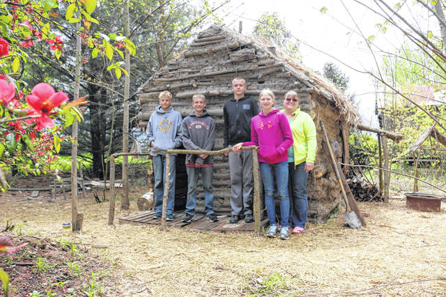 Four of the six Bockey children used their extra time during the COVID-19 pandemic to build a log cabin. Pictured from left are Luke, Zane, Andrew, Olivia and mother Lynn Bockey.