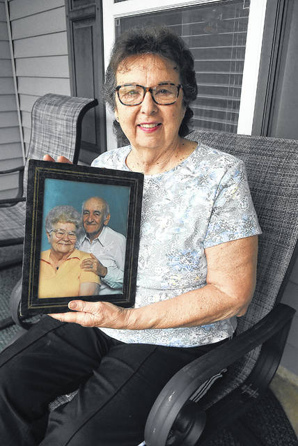 Marcia Etzler, of Van Wert, holds a photograph of her mother and father, Marian and Robert Miller. Marcia is a caregiver for her mother, who was just moved into hospice this week for Alzheimer's. Her late father Robert was also diagnosed with Alzheimer's.