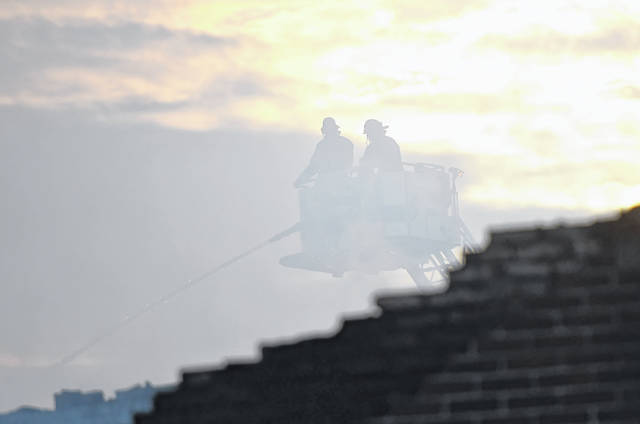 Firefighters from the Lima Fire Department, silhouetted by smoke, douse a fire at National Overstock Liquidation of Ohio, 405 Findlay Road, as the sun rises Monday morning.