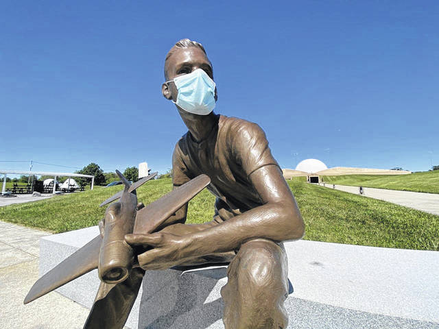 A statue of a young Neil Armstrong outside of the closed Armstrong Air and Space Museum in Wapakoneta fittingly has him wearing a mask.
