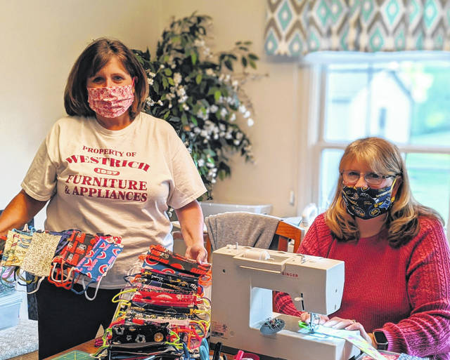 Sandy (Carder) Obermeyer, left, and her sister Sherryl George, of Delphos, started working together to make masks and the effort ballooned.