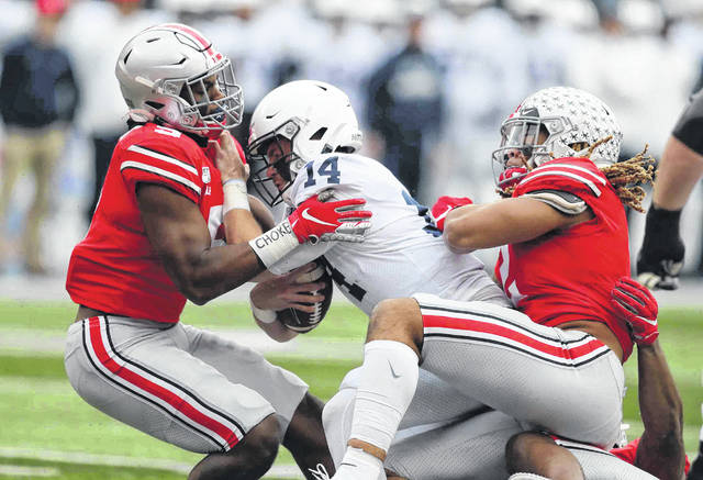 Ohio State's Baron Browning, left, and Chase Young team up to tackle Penn State's Sean Clifford during a game last season at Ohio Stadium in Columbus.