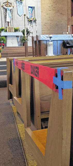 """Red tape reading """"danger"""" blocks two out of every three rows of pews at SS. Peter and Paul Catholic Church in Ottawa, one of the precautions in place this week to ensure social distancing as the Catholic church resumes daily and Sunday services."""