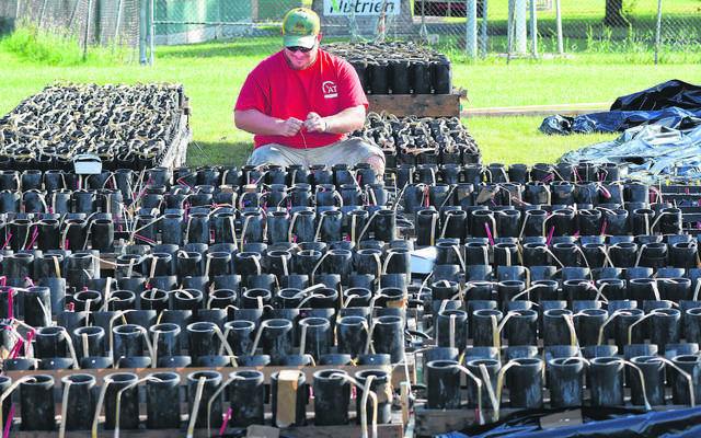Kyle Wagner, a pyrotechnician with Zambelli Fireworks, prepares firework mortar tubes for a computerized firework show for last year's Star Spangled Spectacular at Faurot Park. The annual event was called off for 2020 because of the coronavirus pandemic.