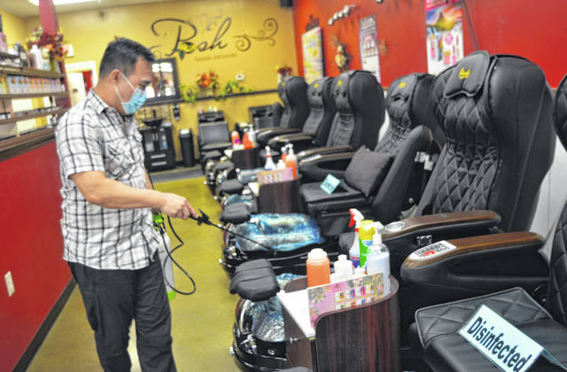 Tony Phung, owner of Posh Nail Spa located at 1931 Elida Road, demonstrates the disinfecting process for cleaning chairs at his recently-opened salon and spa.