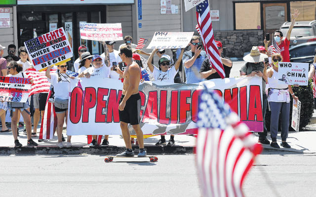 A skateboarder films protesters along Mission Boulevard in Pacific Beach during A Day of Liberty rally on April 26. The protesters were against the government shutdown due to the coronavirus.