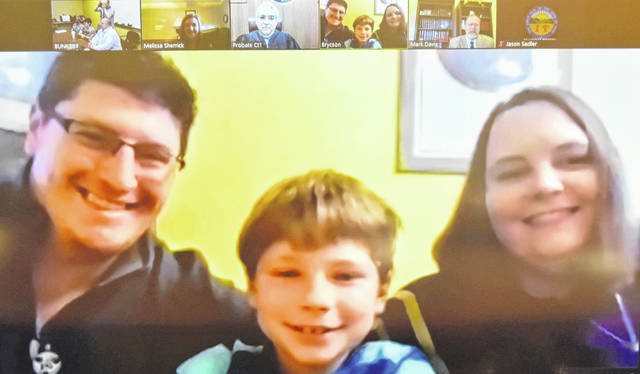 Brycson, center, was the first virtual adoption ever held in Allen County. He was adopted by Andrew, left, and Stephanie Batchelder during a hearing on Zoom software, with court officials and attorneys joining the session.