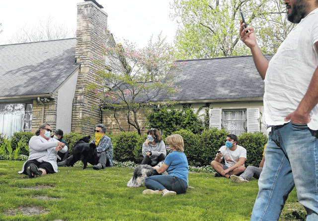 """Supporters of Ohio Health Director Dr. Amy Acton formed a """"friend chain"""" on Acton's front lawn after a few dozen protestors of the Stay at Home orders once again showed up outside of her home in Bexley, a suburb of Columbus, Ohio. The State Highway Patrol now has officers posted at Acton's house."""
