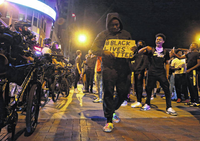 Protesters hold signs and walk past a line of police in downtown Columbus, Ohio, on Thursday during a demonstration over the death of George Floyd in Minneapolis. Columbus police used pepper spray to disperse protesters after some threw plastic bottles of water, smoke bombs and other items at police. Windows at the Statehouse and in bus stations along High Street were shattered, trash cans were tossed and decorative planters wrecked.