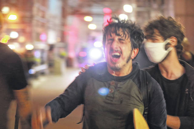 A man in agony after being hit with either tear gas or mace walks down East Broad Street in Columbus as protesters and police clashed on Friday night.
