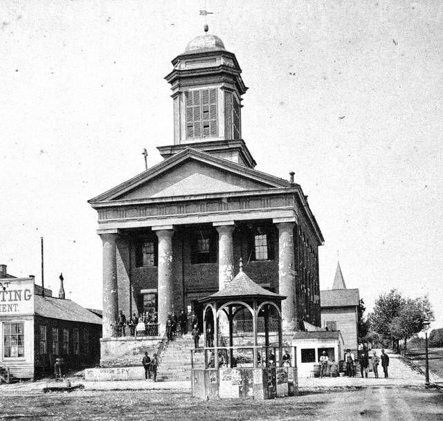 Krebs' photography studio was on the second floor of the old courthouse, pictured, and above Marmon's drug store. Both were in the square. He was also a Methodist Episcopal preacher.