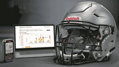A Riddell SpeedFlex helmet sits next to a computer screen displaying information from the InSite tool. Teaming with Catapult, Riddell is providing coaches, players and medical staff detailed information regarding anything from practice regimens to helmet contacts to overall preparation for athletes.