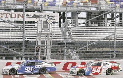 Chase Briscoe (98) crosses the finish line ahead of Kyle Busch (54) to win Thursday's NASCAR Xfinity race in Darlington, S.C.