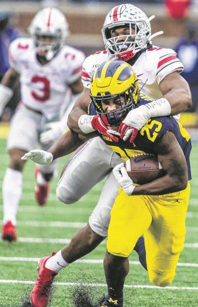 Ohio State's Baron Browning tackles Michigan's Hassan Haskins during a game last season in Ann Arbor, Mich.