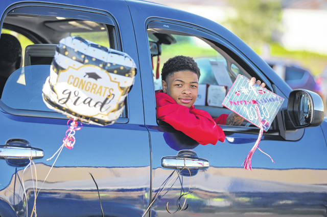 The weather couldn't have been better for Perry graduation festivities Friday night. Above, Chazz Jackson poses for a photo while he waits for his diploma during the Perry drive-through graduation held on Friday evening.