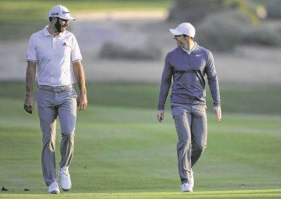 Dustin Johnson, left, and Rory McIlroy will be carrying their bags during today's charity Skins game at Seminole Golf Club in Juno Beach, Florida.