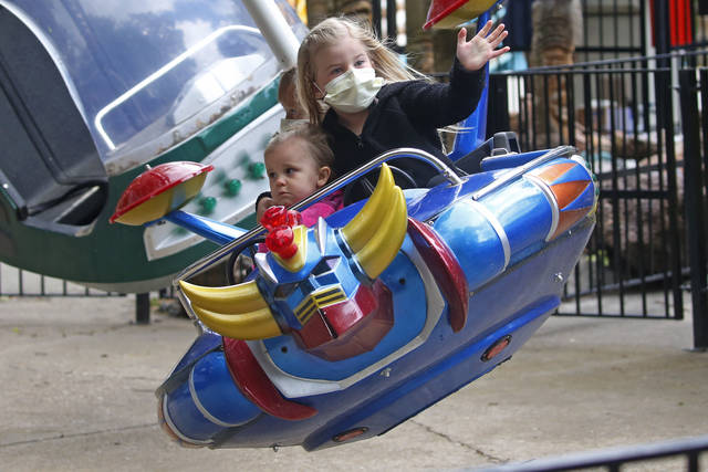 Lennyn, left, and Kassie Paget ride the Moonraker at Lagoon Amusement Park, in Farmington, Utah, on May 25. Amusement parks of all sizes are adjusting everything from selling tickets to serving meals while trying to reassure the public and government leaders that they're safe to visit amid the coronavirus crisis and warnings against large gatherings.