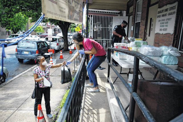 """Lourdes Sherby, center, with Guadalupe Family Services, hands diapers to Louisa Peralta in Camden, N.J., on Thursday. """"I think we're received a lot better than we used to be,"""" said Sgt. Dekel Levy, 41, as he helped hand out diapers to a steady stream of young mothers Thursday afternoon at Guadalupe Family Service."""