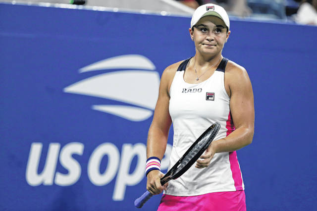 """FILE - In this Aug. 28, 2019, file photo, Ashleigh Barty, of Australia, reacts against Lauren Davis during the second round of the U.S. Open tennis tournament in New York. Barty has joined the ranks of high-profile players concerned over the staging of the U.S. Open while there's still so much uncertainty around the coronavirus pandemic. """"I have concerns too,"""" Barty said in an e-mail to The Associated Press. """"I understand the tournaments are eager to run but keeping everyone safe has to be the priority."""" (AP Photo/Adam Hunger, File)"""