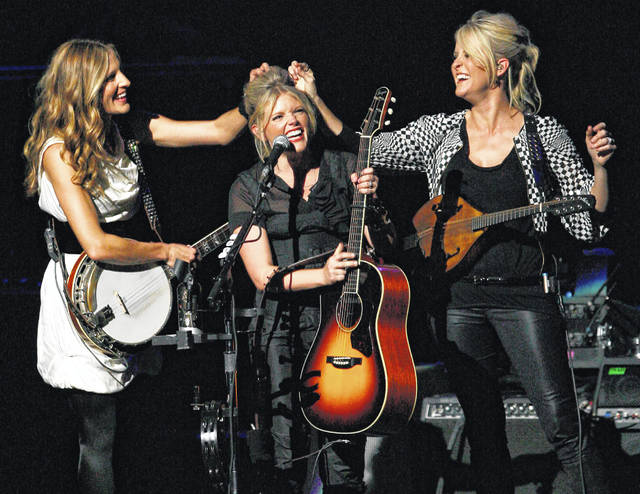 "Emily Robison, left, and Martie Maguire, right, adjust Natalie Maines' hair as the Dixie Chicks perform in Los Angeles in 2007. The Grammy-winning country group dropped the word ""dixie"" from their name and are now going by The Chicks. The move follows a decision by country group Lady Antebellum to change to Lady A after acknowledging the word's association to slavery."