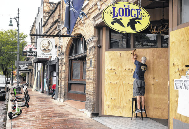 Matthew Gaskamp, general manager of The Lodge, boards up his bar on East 6th Street in Austin, Texas, on Friday after Gov. Greg Abbott closed bars in Texas due to the coronavirus.