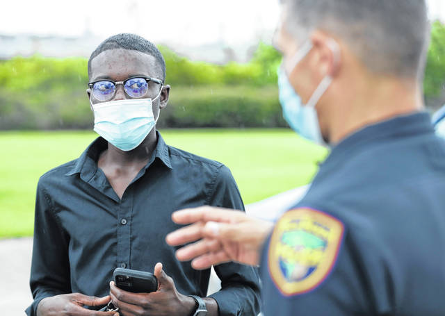 In this June 18 photo, demonstration organizer Weidmayer Pierre, left, talks with Palm Beach Police Capt. Joe Guelli as Guelli gives him a tour of sites that could accommodate protesters in West Palm Beach, Fla. Before the death of George Floyd, business-management student Pierre had planned to spend his Florida summer break working at Wal-Mart. Instead, the 19-year-old has been organizing a protest every few days in Palm Beach County, determined to channel the groundswell of energy around the world into meaningful, peaceful reform in his hometown.