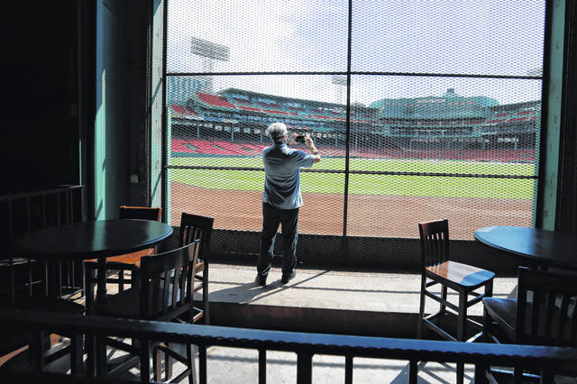 In this June 25, 2020, photo, a reporter photographs the view of the baseball field at Fenway Park from the Bleacher Bar in Boston. Tucked under the center field seats at Fenway Park, down some stairs from Lansdowne Street in an area previously used as the visiting team's batting cage, is a sports bar that is preparing to reopen from the coronavirus shutdown. If Major League Baseball's plans remain on schedule, it may be one of the few places fans will be able to watch a game in person this season. (AP Photo/Elise Amendola)