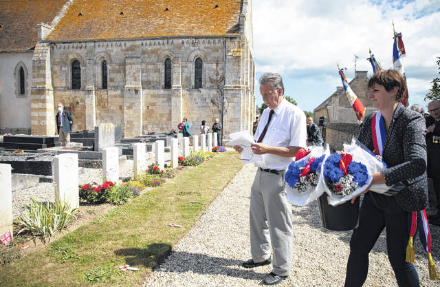 British expatriate Steven Oldrid, left, checks a list as he directs people where to lay wooden crosses with names of WWII dead and flowers during D-Day ceremonies at the local war cemetery in Benouville, Normandy, France on Saturday, June 6, 2020. Due to coronavirus measures many relatives and veterans will not make this years 76th anniversary of D-Day. Oldrid will be bringing it to them virtually as he places wreaths and crosses for families and posts the moments on his facebook page.