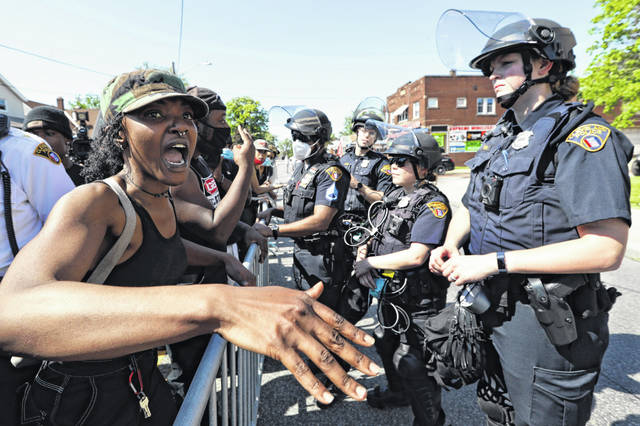 FILE - In this June 2, 2020 file photo, a protester voices her concerns to a Cleveland police officer during a rally for black lives in Cleveland. Ohio would create the first statewide disciplinary database for violent officers and require law enforcement to undergo psychological testing under a proposal unveiled Thursday, June 11, by House Republicans. The legislation comes as the state grapples with the aftermath of civil unrest over the killing of George Floyd in Minneapolis.