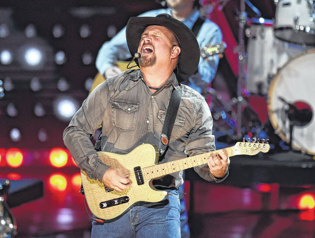 FILE - This March 14, 2019 file photo shows Garth Brooks performing at the iHeartRadio Music Awards in Los Angeles. Brooks is holding a concert in Nashville,Tenn., that will be played at 300 drive-in theaters across the country. Tickets will cost $100 per passenger car or truck.