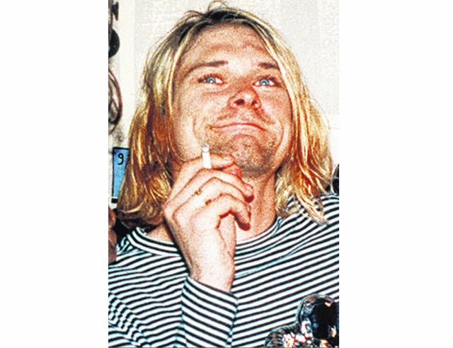 "FILE - This 1993 file photo shows Kurt Cobain, the lead singer of the U.S. rock band Nirvana. Grunge became gold Saturday, June 20, 2020, as the guitar Cobain played on Nirvana's 1993 ""MTV Unplugged"" performance sold for an eye-popping $6 million at auction."