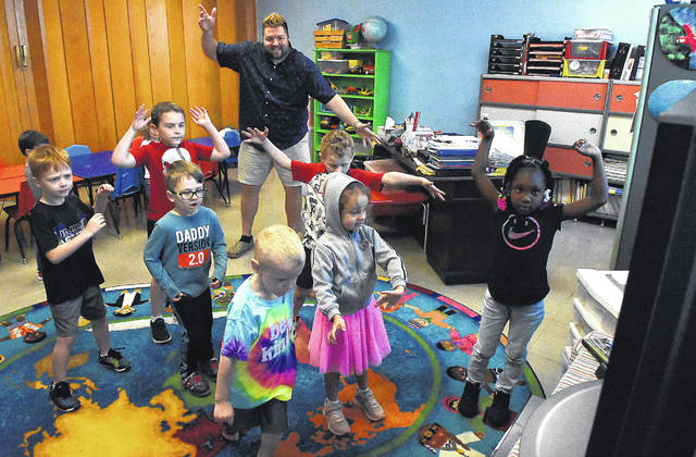 Pre-kindergarten teacher Kyle Ley performs a movement video with students at Trinity United Methodist Church's childcare center on Monday.
