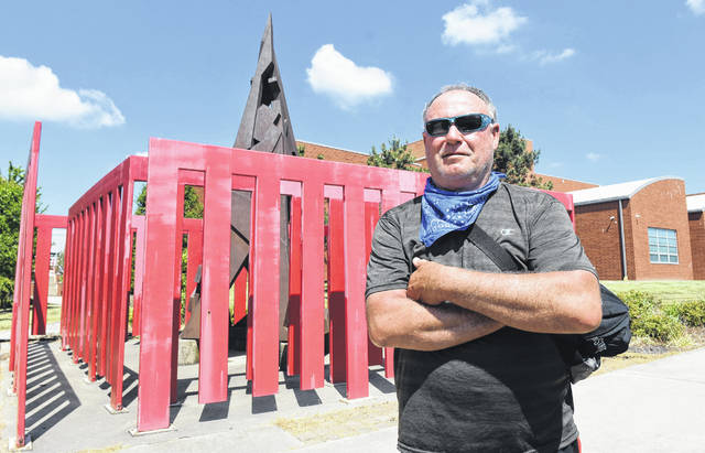 "Russell Hardin of Lima, stands in front of the ""Democracy"" sculpture at Lima Senior High School. Craig J. Orosz 