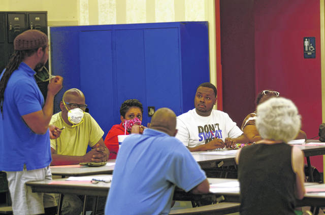 A group of concerned residents meet at Heir Force Community School on Thursday to discuss what can be done to encourage actions for change.