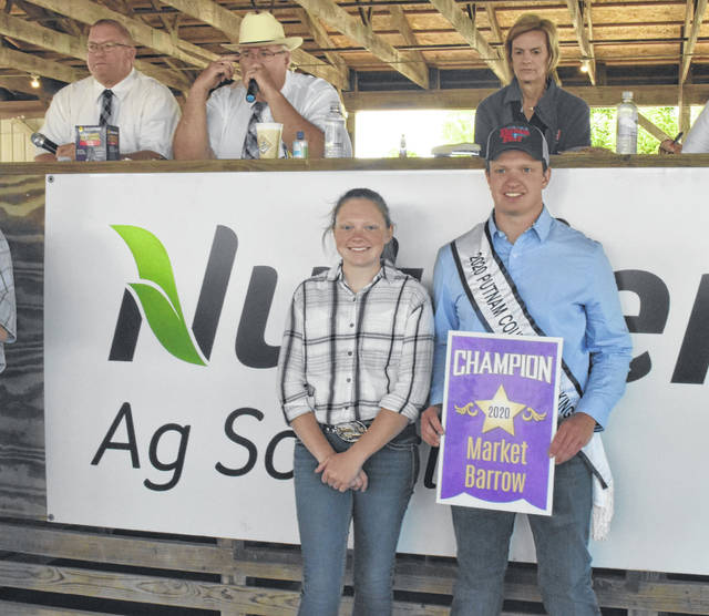 Cody and Paige Meyer, members of the O-G High Risers 4-H club, stood before bidders Thursday at the Junior Fair livestock auction at the Putnam County fair. Due to many restrictions put in place because of the lingering COVID-19 pandemic, livestock remained in the show barns and was not trotted out before bidders this year.